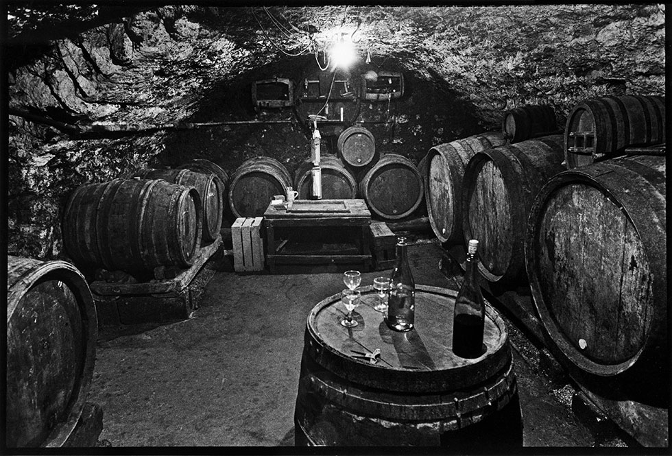 Image of older underground cellar in Northern Rhône of France, with wine barrels, bottles of wine, and glasses