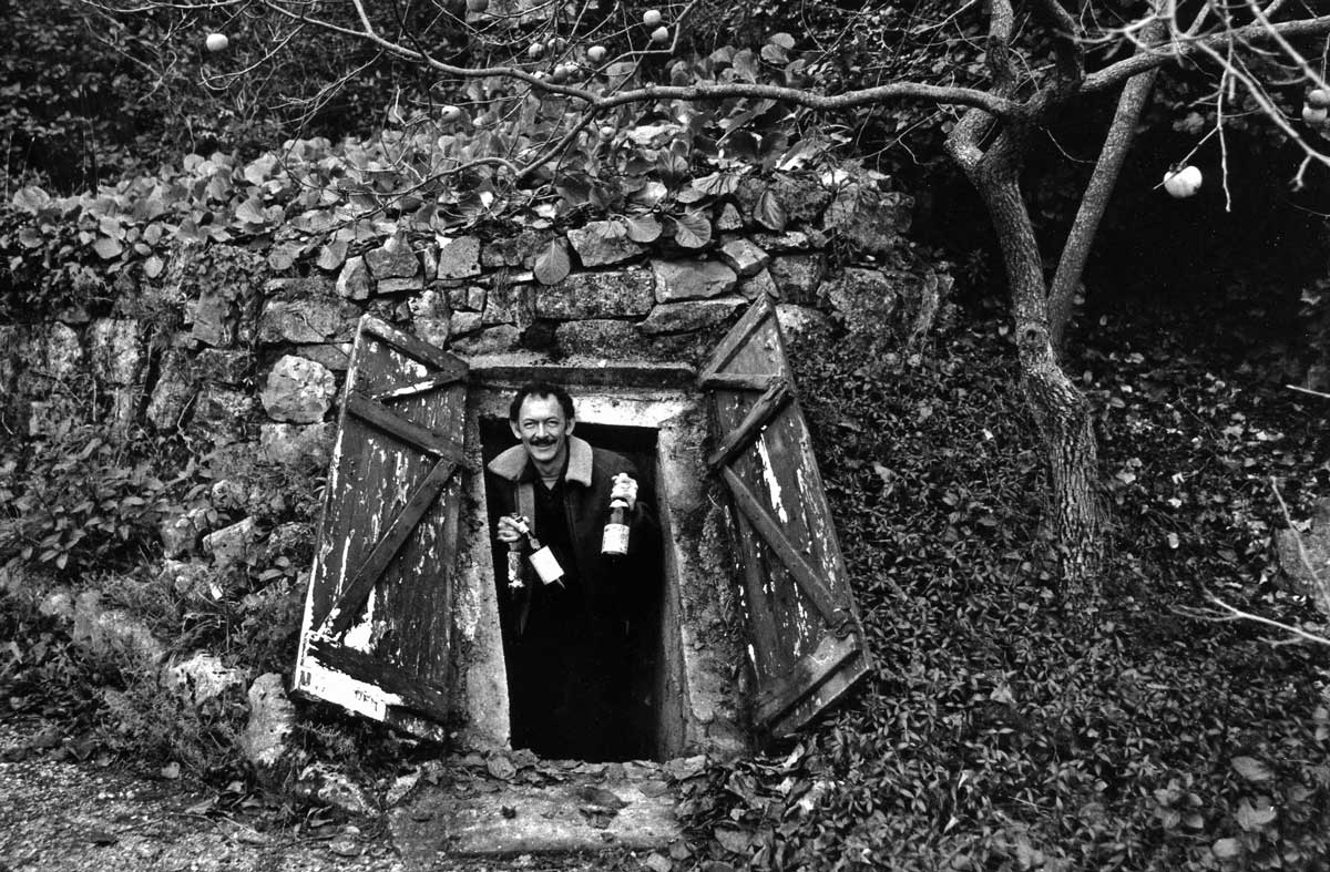 Image of Kermit Lynch emerging from Richard Olney's cellar with wine bottles